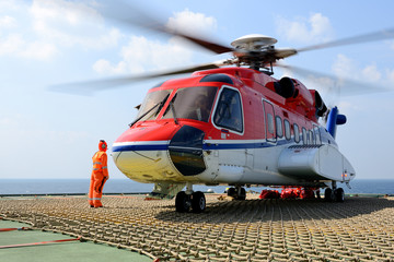 The helicopter landing officer take care loading baggage to heli