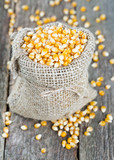 corn in burlap bag on wooden surface