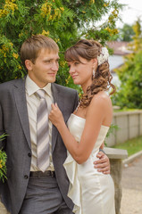 Smiling groom and bride in white dress on background of green tr