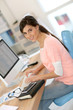 Beautiful girl sitting in office in front of desktop