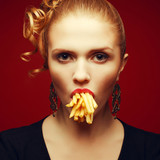 Unhealthy eating. Junk food concept. Girl with fries in mouth