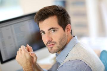 Portrait of office-worker in front of desktop