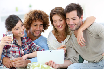 Group of friends looking at pictures on tablet
