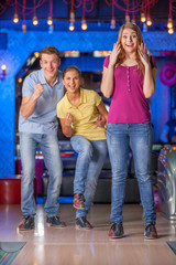 Friends bowling together.
