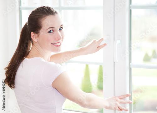 canvas print picture Attraktive Frau schließt Fenster