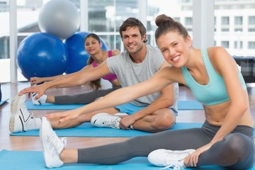 Smiling people doing stretching exercises