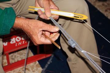 pescatore intento alla riparazione della rete da pesca