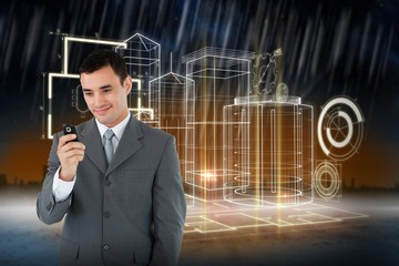 Composite image of smiling businessman looking at his cellphone