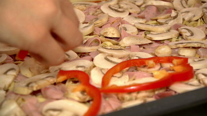 Putting sliced red peppers on pizza