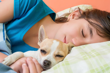 Cute girl hugging and sleeping with her small dog