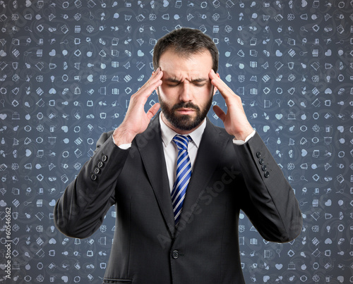 Young businessman with headache over blue background with icons