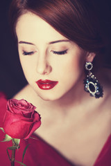 Beautiful redhead women with rose.