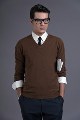 Retro fifties fashion man with dark grease hair. Wearing brown s