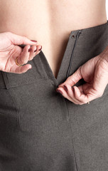 Woman fastening zip on a skirt