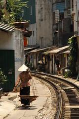 Vietnamese woman walking along a railroad