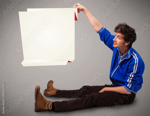 Young man holding white origami paper copy space