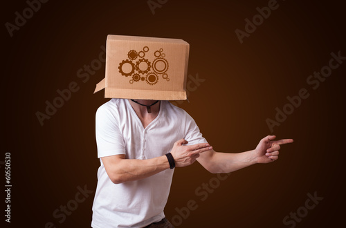 Young man gesturing with a cardboard box on his head with spur w