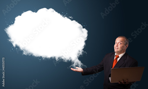 Businessman holding a laptop and presenting abstract cloud copy