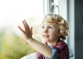 Adorable blond toddler girl looking out of the window