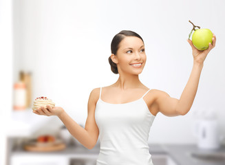 sporty woman with apple and cake in kitchen