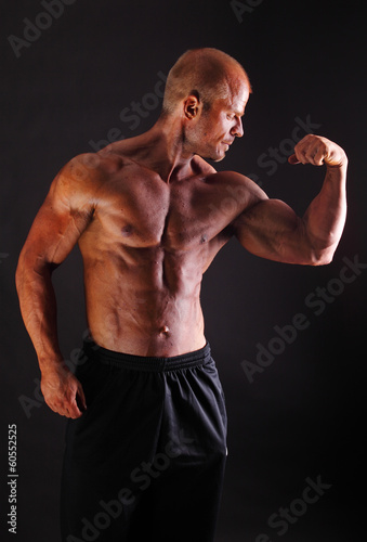 Muscular bodybuilder flexing biceps
