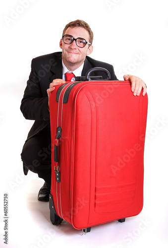 Young business man behind red luggage