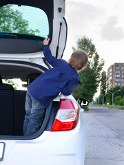 Little boy leaning out of the back of a car