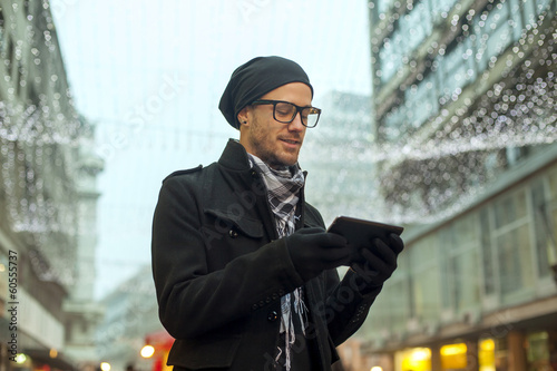 Man holdin i-pad tablet computer on street
