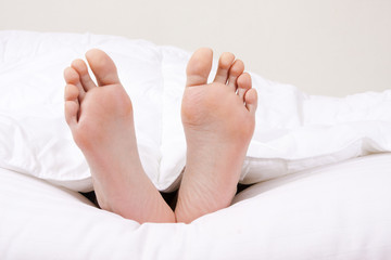 feet in the foreground in the covered bed