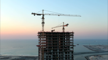 Cranes at a skyscraper construction. time lapse