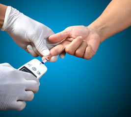 Doctor testing a patients glucose level after pricking his finge