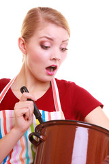 Shocked housewife chef in kitchen apron with pot of soup ladle
