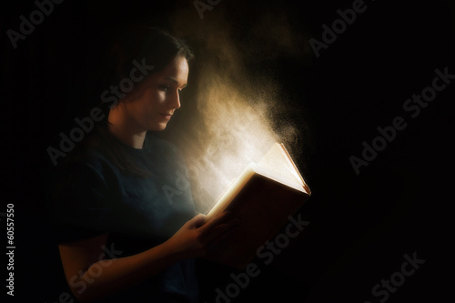 Reading a glowing book - 60557550
