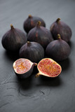 Ripe fig fruits over black wooden background, close-up