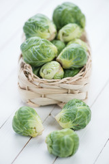 Wicker basket with brussels sprouts, white wooden background