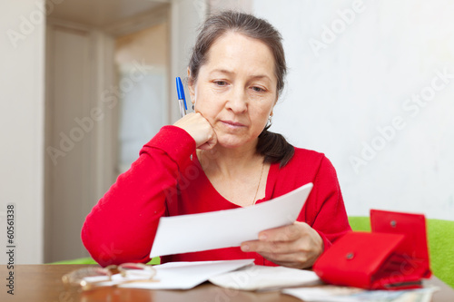 mature woman reads payment documents
