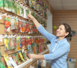 mature woman chooses  seeds at store
