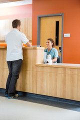 Patient Conversing With Nurse At Reception Desk