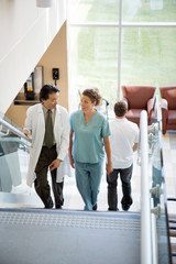 Doctor And Nurse Discussing While Walking On Stairs