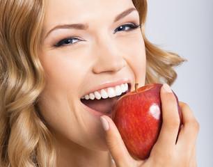 Woman eating apple, on grey