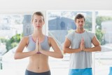 Couple with joined hands and eyes closed in fitness studio