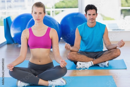 Young couple sitting in lotus posture at fitness studio