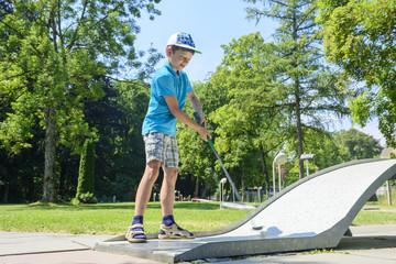 Junge spielt Minigolf