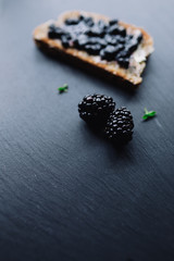 Healthy breakfast with blackberry jam with toast on black slate