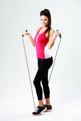 Young happy woman with jumping rope on a gray background