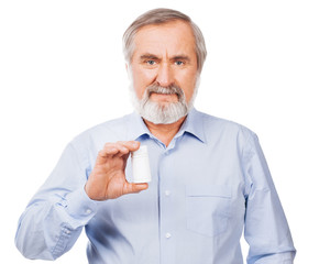 Senior man showing pills isolated on white