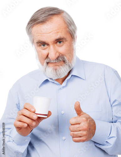 Smart old man drinking cup of coffee and showing sign OK