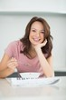 Smiling woman with bowl of cereals reading newspaper in kitchen