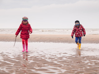 small boy and girl paddling on the beach