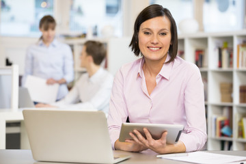 Portrait of pretty Businesswoman working on computer in office